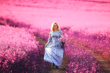 girl in a field of lilac flowers in lavender colors, violet and pink landscape, happy and harmony