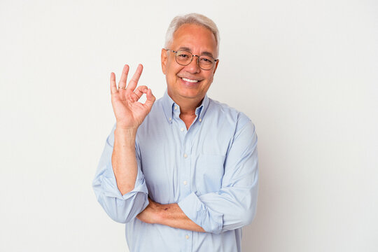 Senior american man isolated on white background winks an eye and holds an okay gesture with hand.