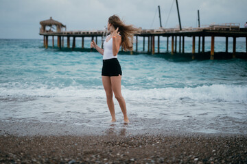 Fototapeta Wiatr we włosach - kobieta na plaży - wakacje all inclusive w Turcji obraz
