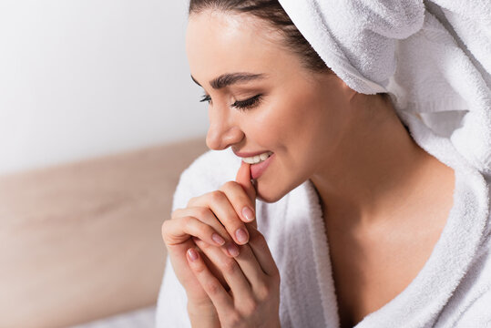 happy woman in towel on head biting nail