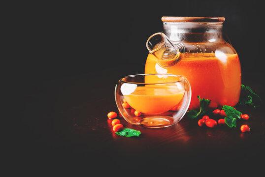 tea pot and Cup of sea buckthorn tea on black background
