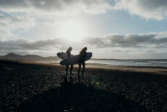 Couple with surfboards walking on island