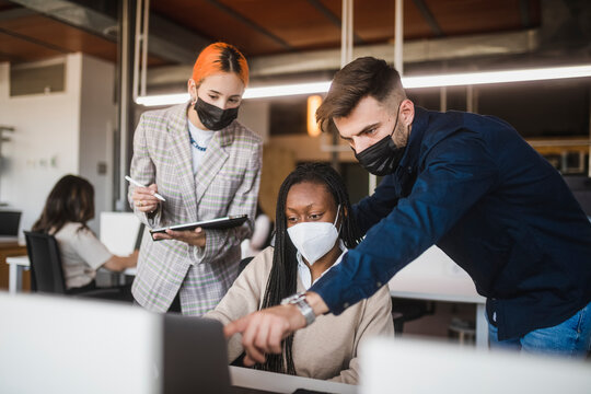 Company of multiethnic colleagues in masks working together in office