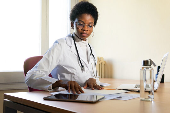 Black female doctor working with papers in office