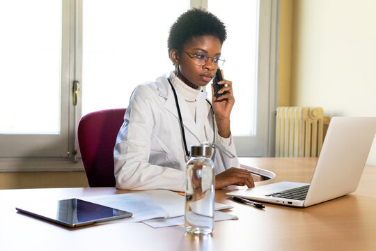 Doctor with laptop and smartphone working in office