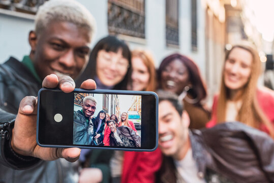 Man taking selfie with group of diverse friends
