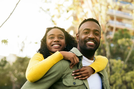 smiling black man giving piggyback ride to his girlfriend.front view