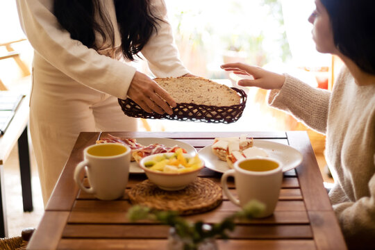 Mother giving bread toast to her daughter at breakfast