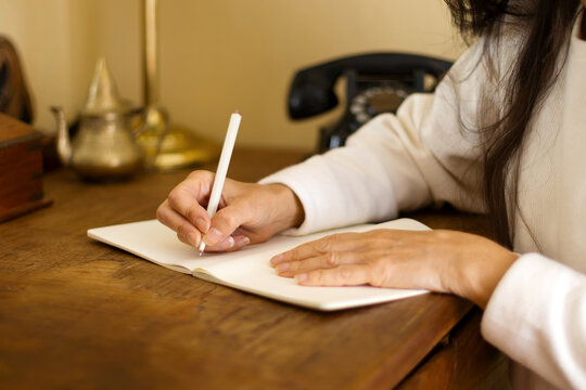 woman writing in a notebook on a wooden desk.
