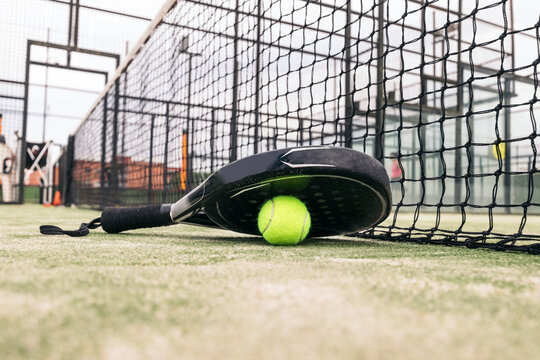 paddle tennis racket and ball on the court