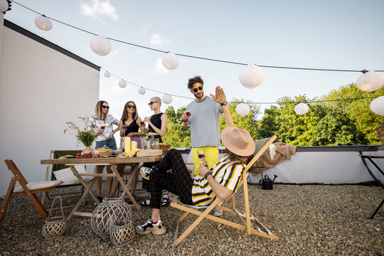 Young group of stylish people having a festive dinner on the roof terrace. Hipsters hanging out and having great summertime together outdoors