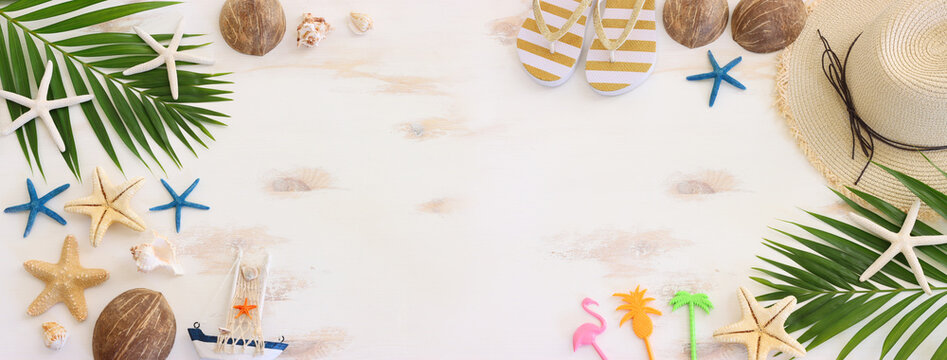 nautical concept with decorative sail boat, seashells over white wooden background