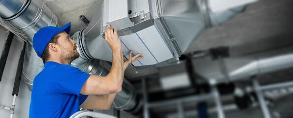 Fototapeta ventilation system installation and repair service. hvac technician at work. banner copy space obraz