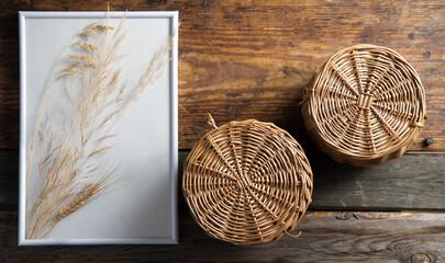 Obraz Dekoracja z ramki z koszyków wiklinowych na starych drewnianych deskach - fototapety do salonu