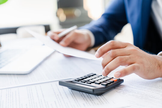 Businessman counting bills savings investments dividends on calculator, managing money to make income and doing paperwork. Saving money and investing concept. Paying bills
