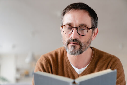 Relaxed pensive middle-aged mature man freelancer tutor adult student lecturer reading book at home, preparing for exams at university, enjoying novels at leisure time.
