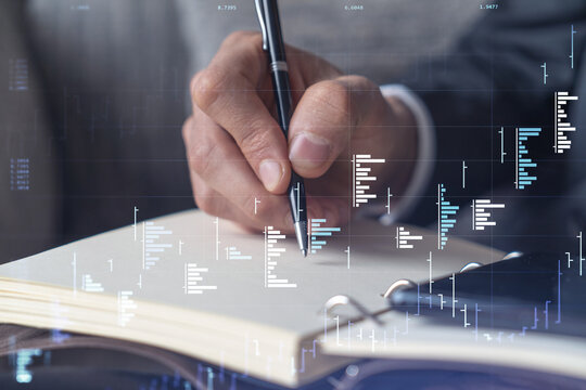 A trader in formal wear writing down some quotes to research stock market trends using smart phone for right investment solutions. Wealth management concept. Hologram Forex chart over close up shot.