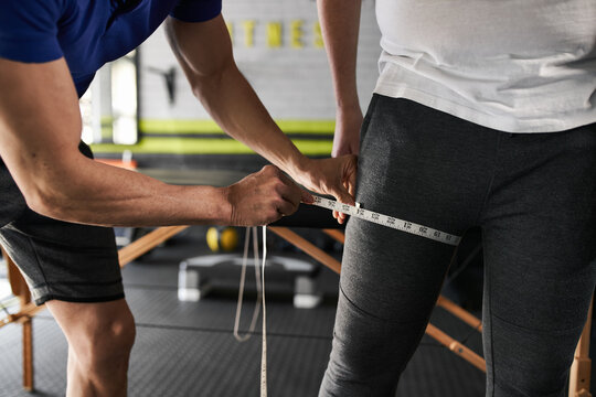 Close up unrecognizable personal trainer measuring thigh