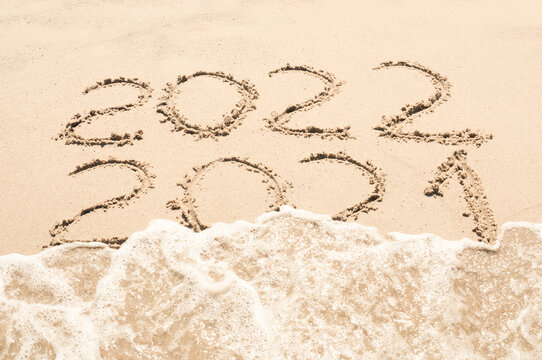 Inscription 2021 and 2020 numbers written on sand.  New Year 2022 replace 2021. Concept on the sea beach