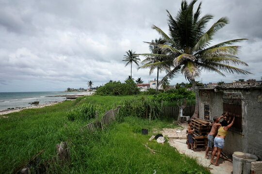 A couple prepare a window of their home for the arrival of Storm Elsa, Guanabo, Cuba