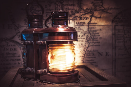 Old vintage light lantern with old antique map on background as adventure background