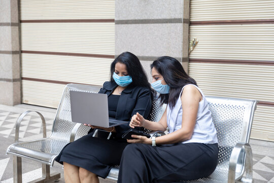 Two Indian woman wearing Covid-19 protection mask having a discussion on their laptop in an urban corporate setting.