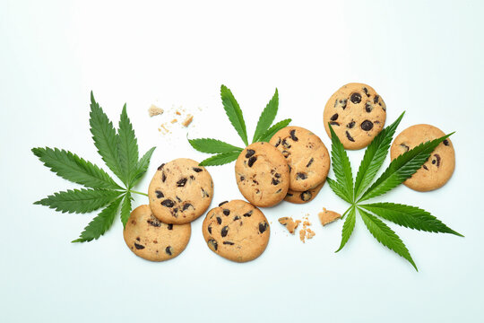 Cannabis leaves and cookies on white background