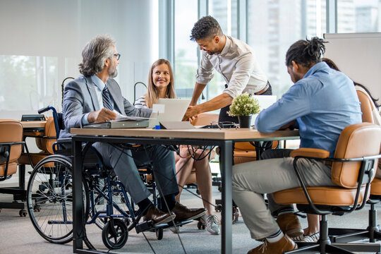 Happy businessman in wheelchair reading documents during a meeting with his colleagues in the office. Shot of a team of businesspeople having a meeting in a modern office