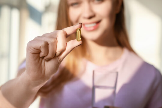 Young woman taking fish oil at home, closeup