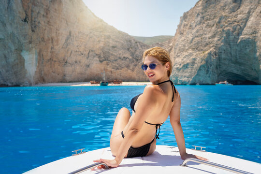 Attractive, blonde woman in bikini sits on a yacht and enjoys her summer holidays at the turquoise waters of the Ionian Sea, Zakynthos island, Greece
