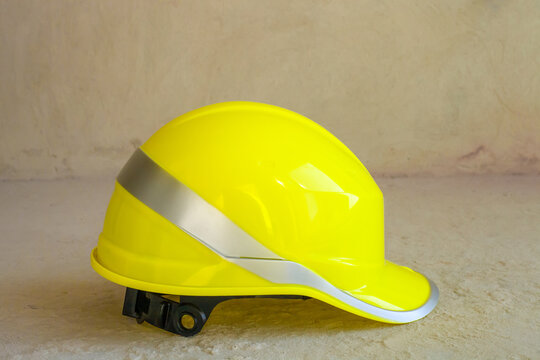 Yellow hardhat. Construction worker safety helmet on concrete floor in house, side view