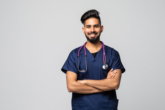 Smiling indian male doctor in white coat with stethoscope over grey background