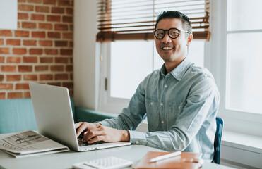 Fototapeta Asian businessman in an office using a laptop obraz