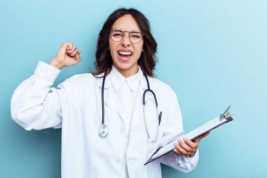 Young doctor mexican woman isolated on blue background raising fist after a victory, winner concept.