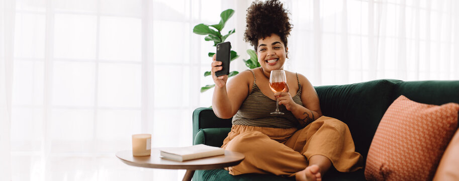 Woman having wine and video call frineds using cell phone
