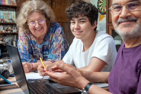 Grandparents and Teenage Boy at Home Gathered around Laptop Smiling