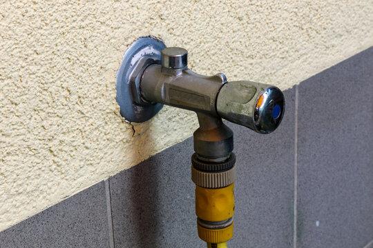 Hauswand mit Außenwasserhahn mit Gefrierschutz und  Schlauchanschluss