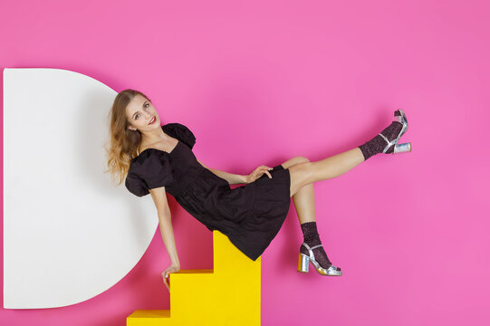 Young sweet woman in a black dress poses in the studio against a pink wall