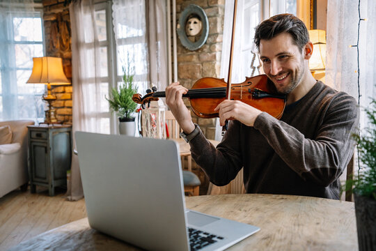 Man student learns to play the violin online using a laptop.