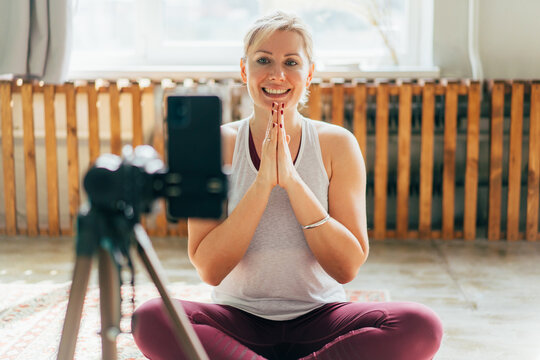 A modern yoga instructor welcomes the community to a lesson in online streaming and records the lesson on a phone camera. Online classroom teaching.