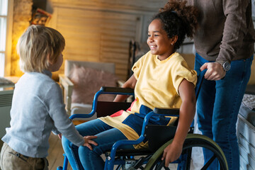 Fototapeta Happy multiethnic family. Smiling little girl with disability in wheelchair at home obraz