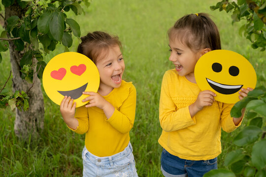 Two little funny girls are holding smile faces with different emotions in their hands. Children are having fun in the park. World emoji Day. Anthropomorphic smiley face.