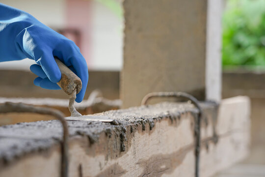 wear glove hand of industrial bricklayer hold  aluminium brick trowel installing mortar wall on construction site, selective focus