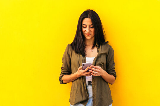 Young stylish woman using her mobile leaning on a yellow wall