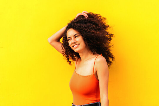 Beautiful afro woman leaning on a yellow wall