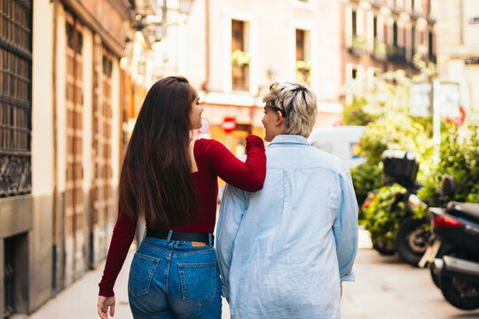 Back view of two teenager girls walking on a city street