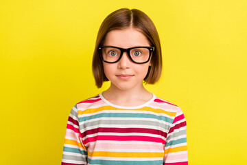 Photo of adorable young cute small girl wear glasses charming face smart isolated on yellow color background Wall mural