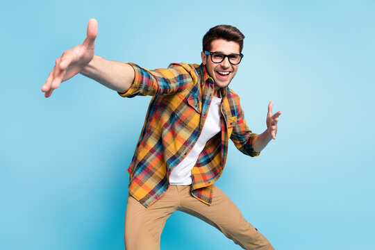 Photo of sweet funky young gentleman wear checkered shirt glasses dancing smiling isolated blue color background