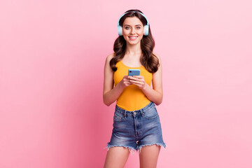 Photo of cute adorable woman wear yellow singlet listening music holding modern gadget empty space isolated pink color background Wall mural
