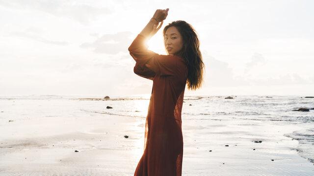 Stylish ethnic woman standing on beach